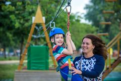 Adorable little boy enjoying his time in a rope playground structure at adventure park,. His mother giving a helping hand to him, family weekend activities Stock Images