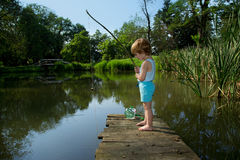 Adorable Little Boy Fishing from Wooden Dock on a Lake on Sunny Day Royalty Free Stock Image
