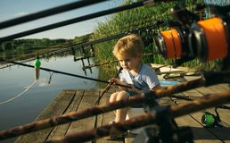 Adorable little boy fishing from wooden dock on lake royalty free stock photography