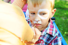 Adorable little boy getting her face painted. Children painted Stock Image