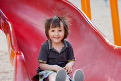 Adorable little boy, going down a slide, smiling at camera Royalty Free Stock Images
