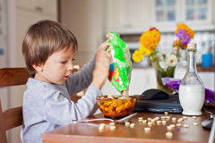 Adorable little boy, having cereals for breakfast while watching Royalty Free Stock Images