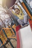 Cute smiling boy playing on slide in park stock images
