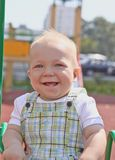 Adorable little boy having fun on a swing outdoor Royalty Free Stock Images