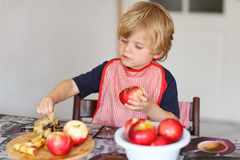 Adorable little boy helping and baking apple pie in home''s kitc Royalty Free Stock Photos