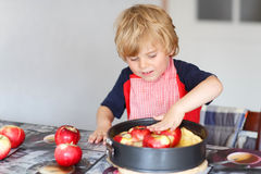 Adorable little boy helping and baking apple pie in home''s kitc Royalty Free Stock Image