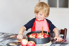 Adorable little boy helping and baking apple pie in home''s kitc Stock Photos