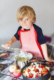 Adorable little boy helping and baking apple pie in home''s kitc Royalty Free Stock Photo