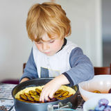Adorable little boy helping and baking plum pie Royalty Free Stock Photo
