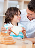 Adorable little boy and his father eating bread Royalty Free Stock Image