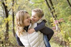 Adorable little boy with his mother in autumn park Royalty Free Stock Photos