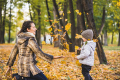 Adorable little boy with his mother in autumn park. Mother and son throws yellow leaves Stock Images