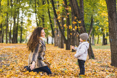Adorable little boy with his mother in autumn park. Mother and son throws yellow leaves Stock Photo