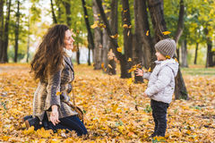 Adorable little boy with his mother in autumn park. Mother and son throws yellow leaves Royalty Free Stock Photography