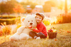 Adorable little boy with his teddy bear friend in the park on su Stock Photos