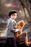 Adorable little boy with his teddy bear friend in the park Royalty Free Stock Photo