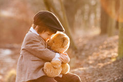 Adorable little boy with his teddy bear friend in the park Stock Photography