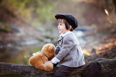 Adorable little boy with his teddy bear friend in the park Stock Image