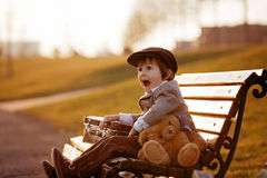 Adorable little boy with his teddy bear friend in the park Stock Photo