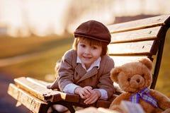 Adorable little boy with his teddy bear friend in the park Stock Photos