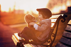 Adorable little boy with his teddy bear friend in the park Stock Images