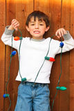 Adorable little boy holding Christmas lights with funny smile. Cute young kid in front of wood fence with funny frown expression holding a strand of lights for Stock Image