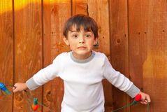 Adorable little boy holding Christmas lights looking surprised. Royalty Free Stock Photos
