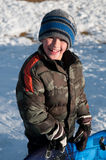 Adorable little boy holding sled smiling at camera wearing camo Stock Images