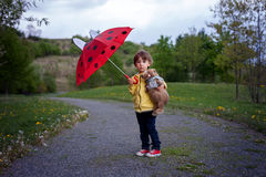 Adorable little boy, holding toy friend and umbrella Stock Photo