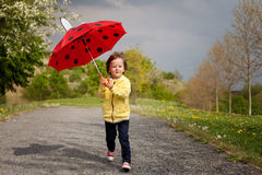 Adorable little boy, holding umbrella, running in a park Royalty Free Stock Image