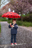Adorable little boy, holding umbrella, walking in a park Royalty Free Stock Image