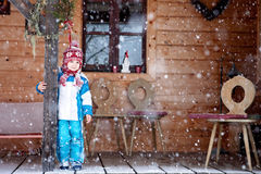 Adorable little boy with lantern, standing in front of a winter Stock Photography