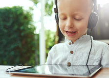 Adorable little boy listening to recorded music Royalty Free Stock Images
