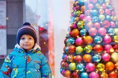 Adorable little boy looking through the window at Christmas deco Stock Photos