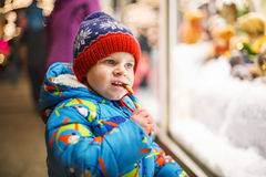 Adorable little boy looking through the window at Christmas deco Royalty Free Stock Photos