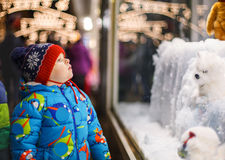 Adorable little boy looking through the window at Christmas decoration in the shop royalty free stock image