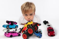 Adorable little boy lying all surrounded by car toys with his cute cheeks and lips ready to kiss someone. A handsome small child with fair hair and blue eyes stock photography