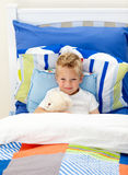Adorable little boy lying in bed Stock Photo