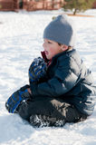 Adorable little boy in navy coat sitting in snow. Stock Photos