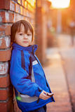 Adorable little boy, next to brick wall, eating chocolate bar on Stock Photo