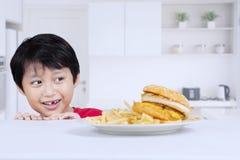 Adorable little boy peeking a delicious hamburger Royalty Free Stock Photo