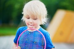 Little boy playing badminton with mom on the playground Royalty Free Stock Photo
