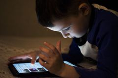 Adorable little boy playing on a digital tablet. Boy looking at digital tablet. Parental permission concepts, safety online. Internet for child stock images