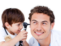 Adorable little boy playing with the doctor Stock Photos