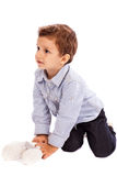 Adorable little boy playing with his toy bear on the floor Stock Photos