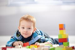 Adorable little boy playing at home. Adorable little boy playing with building cubes at home, laying on floor Stock Images