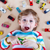 Adorable little boy playing with lots of toy cars indoor Stock Photos