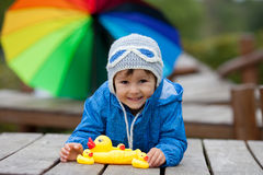 Adorable little boy, playing with rubber ducks outside on an aut Stock Photo