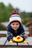 Adorable little boy, playing with rubber ducks outside on an aut Stock Image