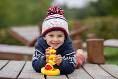 Adorable little boy, playing with rubber ducks outside on an aut Stock Images